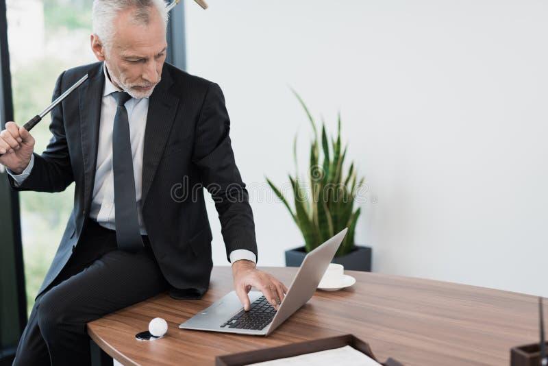 Un homme respectable plus âgé posant dans son bureau avec un club de golf Il s'assied sur le bureau derrière l'ordinateur portabl photographie stock