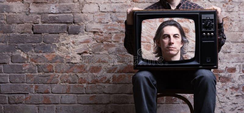 Un homme retenant une rétro télévision photos libres de droits