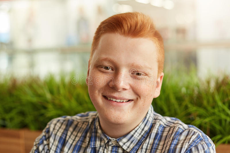 Un homme roux positif avec des taches de rousseur ayant la coiffure élégante utilisant la chemise vérifiée souriant tout en regar images libres de droits