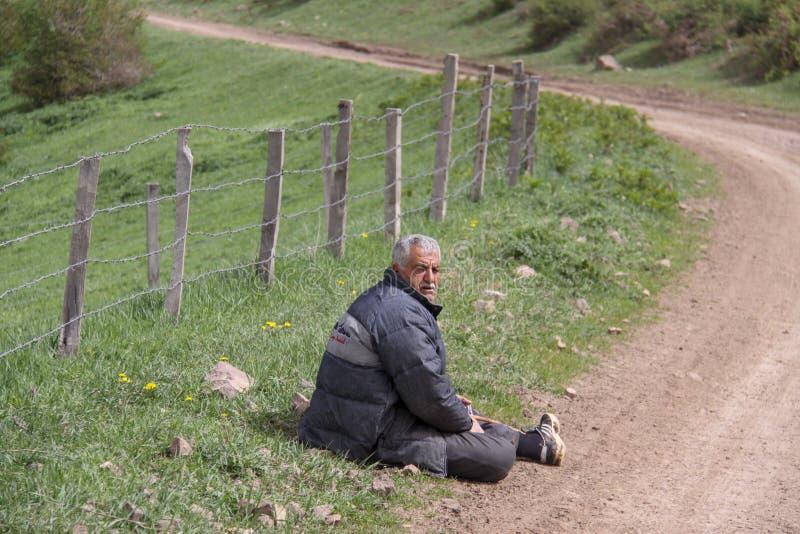 Un homme rural fatigué s'asseyant à côté de la route sur le plancher, une ferme est enfermé avec une barrière, Iran, Gilan image libre de droits