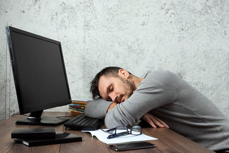 Un homme, un homme s'asseyant à une table dans le bureau, et ne travaillant pas, regard fatigué Le concept du travail de bureau,  photos libres de droits