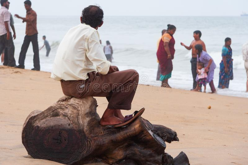 Un homme s'asseyant sur un tronçon d'arbre regarde fixement vers la mer agitée comme transhorizon photo stock