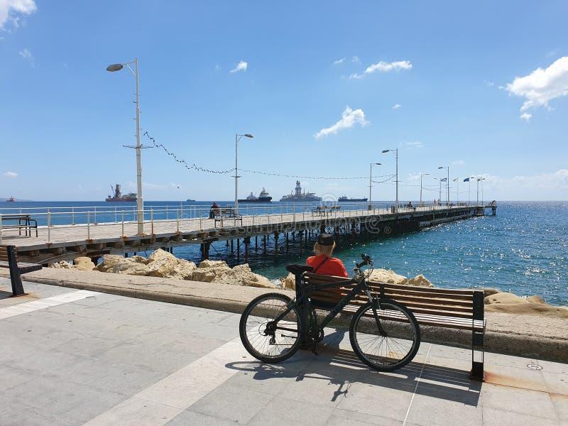 Un homme s'assied sur un banc derrière des regards fixes d'une bicyclette vers la mer à la promenade de Molos à Limassol, Chypre photos libres de droits