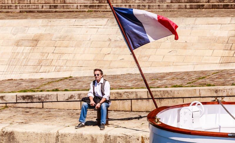 Un homme s'assied sur le remblai à côté du drapeau français seine moderne de fleuve de Paris de passerelle photos libres de droits