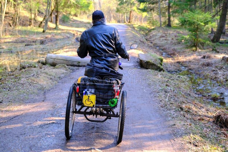 Un homme sans abri dans des tours d'un fauteuil roulant sur un chemin forestier Le fauteuil roulant ? trois roues est ?quip? d'un image stock