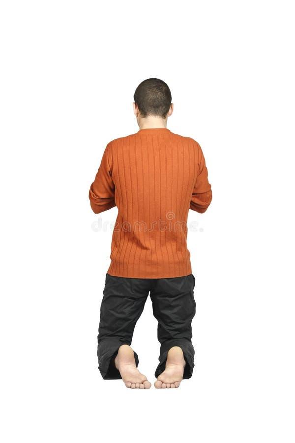 Un homme se mettant à genoux avec le sien en arrière image stock