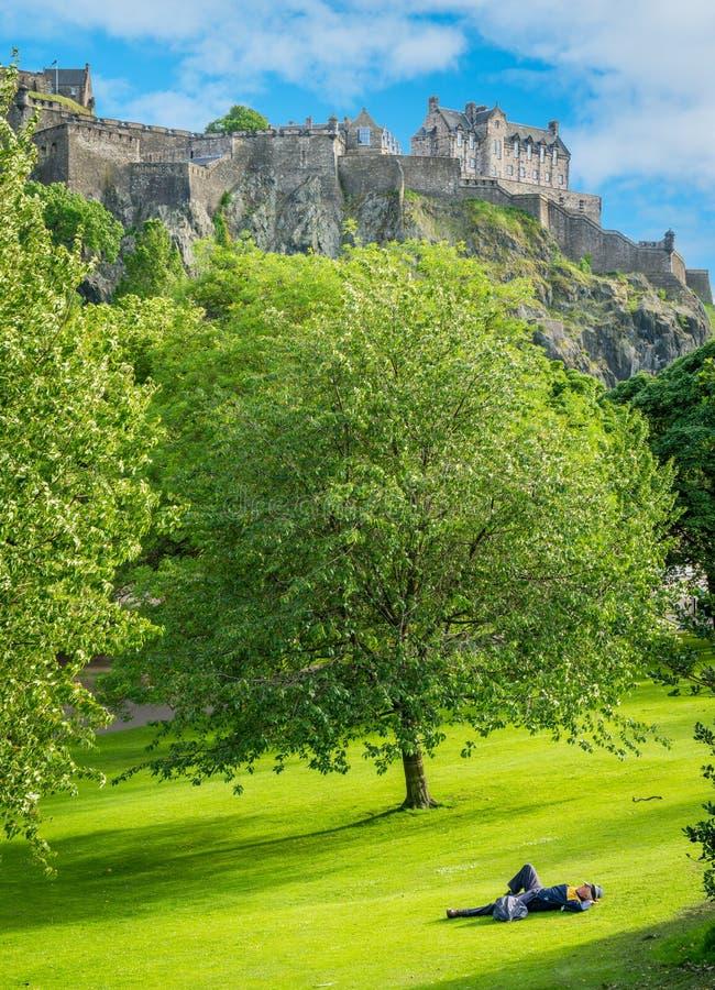 Un homme se reposant dans princes Street Gardens avec le château d'Edimbourg à l'arrière-plan l'ecosse photos libres de droits