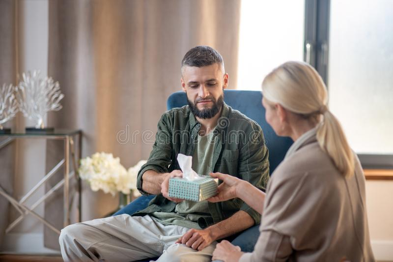 Un homme se sentant reconnaissant en prenant des serviettes de la part d'un psychologue photo stock