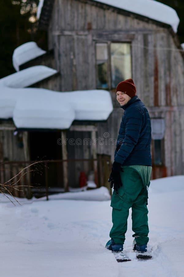 Un homme se tient sur des skis dans la forêt sur le fond d'une vieille maison en bois photos stock