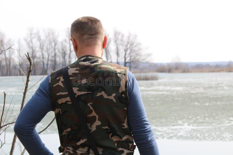 Un homme se tient sur le rivage et regarde fixement photo libre de droits