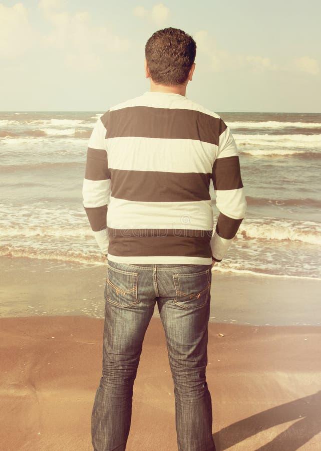 Un homme se tient sur le sable de la plage images libres de droits