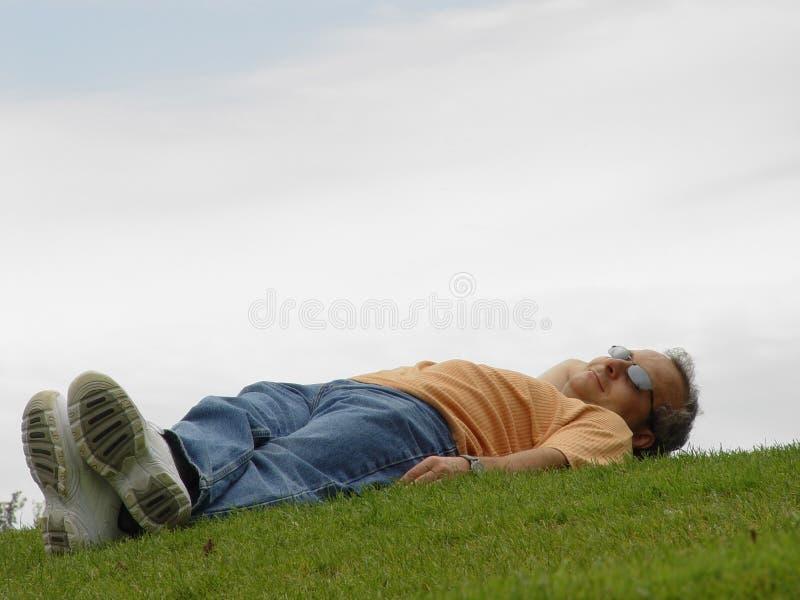 Un homme se trouvant sur l'herbe image stock