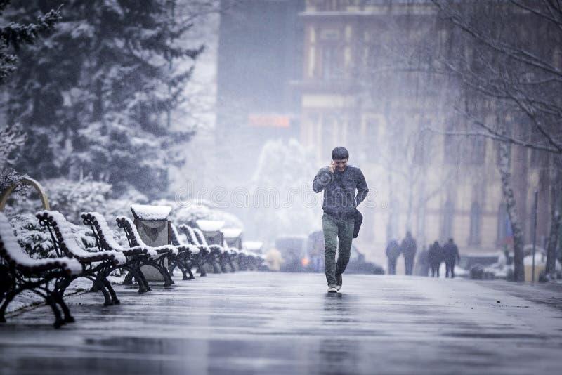 Un homme seul marchant en hiver froid parlant au téléphone photo stock