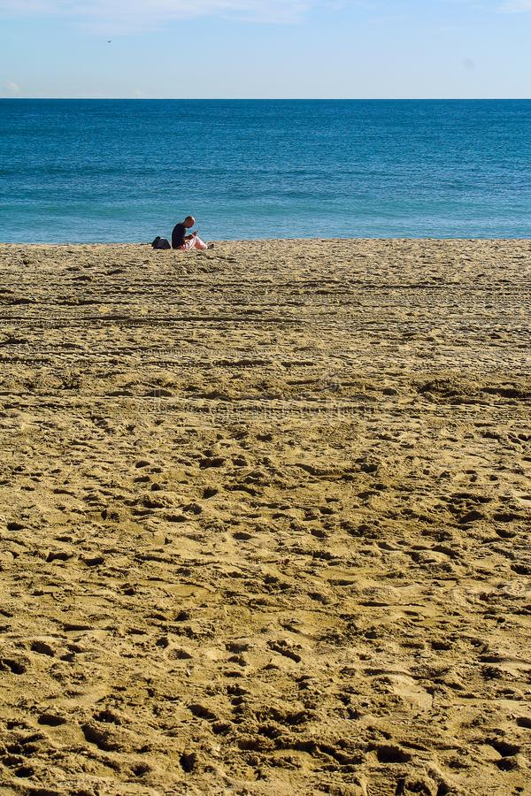 Un homme seul s'asseyant sur la plage images libres de droits