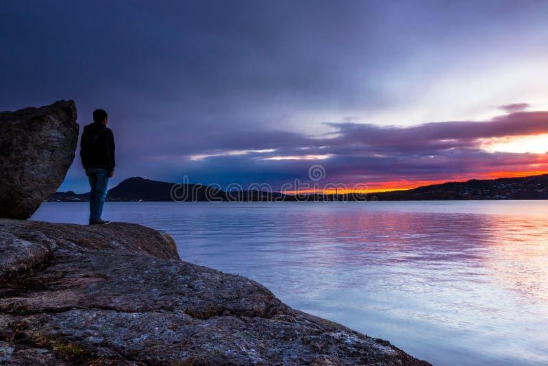 Un homme seul se tenant avec son Thoughs chez Suset coloré image libre de droits