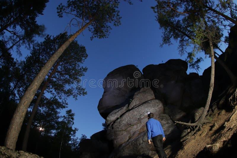 Un homme seul se tient au pied de la montagne et regarde le ciel inconnu Ciel étoilé dans la nature sibérienne image libre de droits