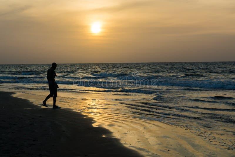 Un homme silhoutted sur la plage de Kotu, Gambie image libre de droits