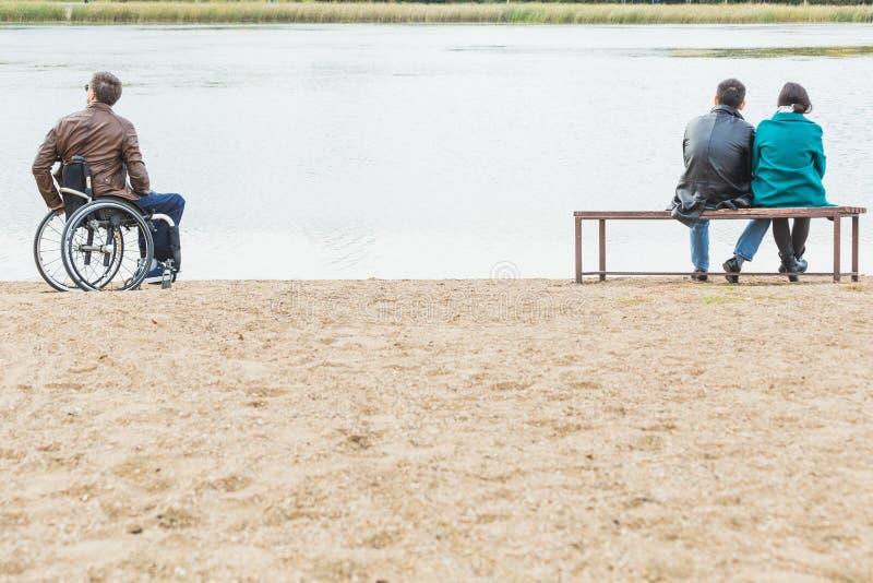Un homme solitaire dans un fauteuil roulant et un couple sur un banc de parc images libres de droits