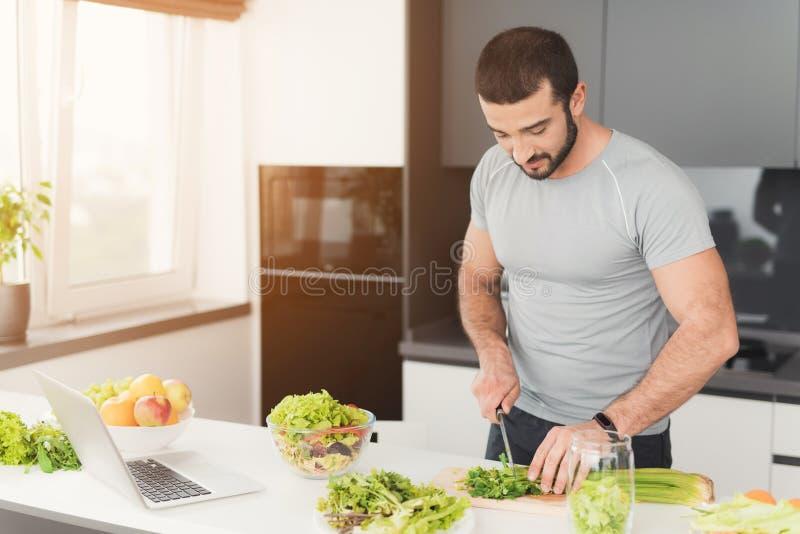 Un homme sportif prépare une salade dans la cuisine Il coupe les feuilles de la laitue et les met dans un pot photo stock