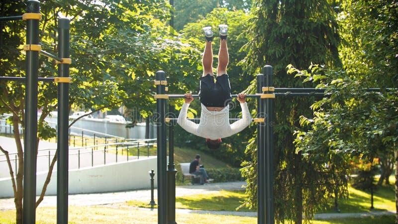 Un homme sportif s'exerçant sur la barre horizontale - roule plus de photos stock