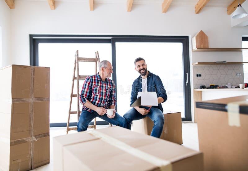 Un homme supérieur aidant son fils avec fournir la nouvelle maison, un nouveau concept à la maison photos libres de droits