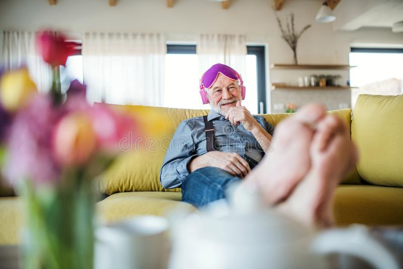 Un homme supérieur avec les écouteurs et le masque d'oeil se reposant sur le sofa à l'intérieur à la maison photo libre de droits