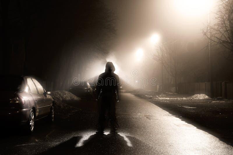 Un homme sur la rue brumeuse la nuit images stock