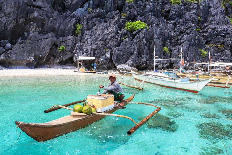 Un homme sur le petit paraw à la mer de l'EL Nido, Philippines photographie stock