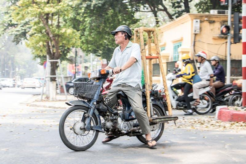 Un homme sur une moto porte une grande construction en bois photo stock