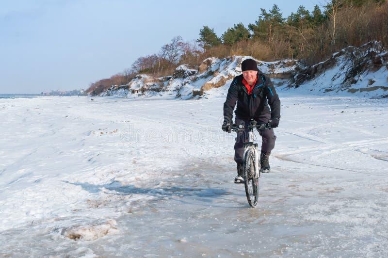 Un homme sur un vélo monte en hiver, tours de cycliste sur la neige photos stock