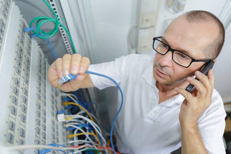 Un homme tenant un câble électrique avec un téléphone portable demandant de l'aide photo stock