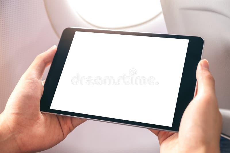 Un homme tenant et regardant le PC noir de comprimé avec l'écran de bureau blanc de blanc à côté d'une fenêtre d'avion photos stock