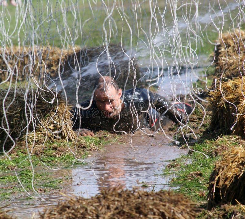 Un homme terrifié rampant dans la boue photos stock