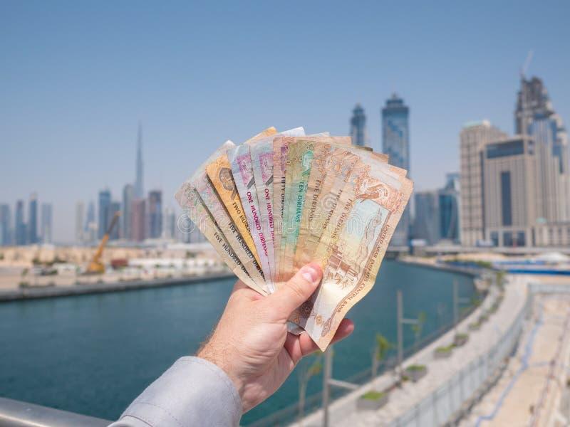 Un homme tient l'argent des Emirats Arabes Unis Dirham photographie stock libre de droits