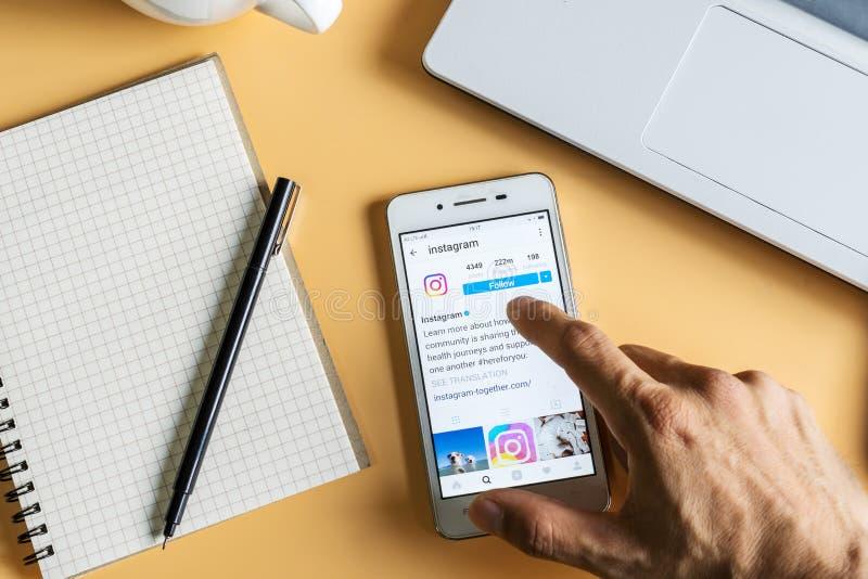 Un homme tient le téléphone intelligent avec l'application d'Instagram sur l'écran image stock