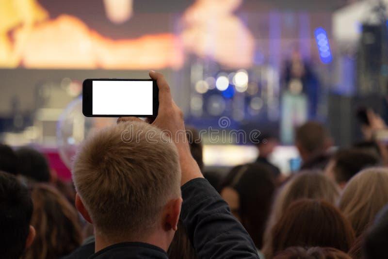 Un homme tient un smartphone dans des ses mains et l'enregistre ou vit annonçant un concert de rue parmi une foule des fans Vue d photo stock