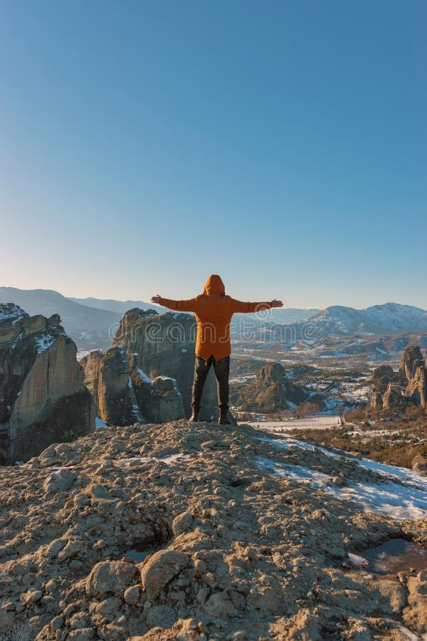 Un homme tient sur les montagnes rocheuses et apprécie la belle vue du monastère de Meteora en Grèce image libre de droits