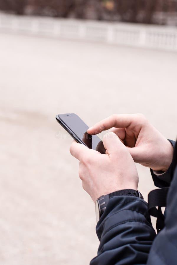 Un homme tient un téléphone portable dans sa main photo stock