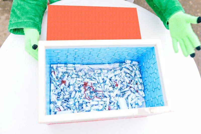 Un homme tient une bo?te bleue Sur les mains de porter les gants verts Dans la bo?te il y a les notes pli?es dans un tube Un cube images libres de droits