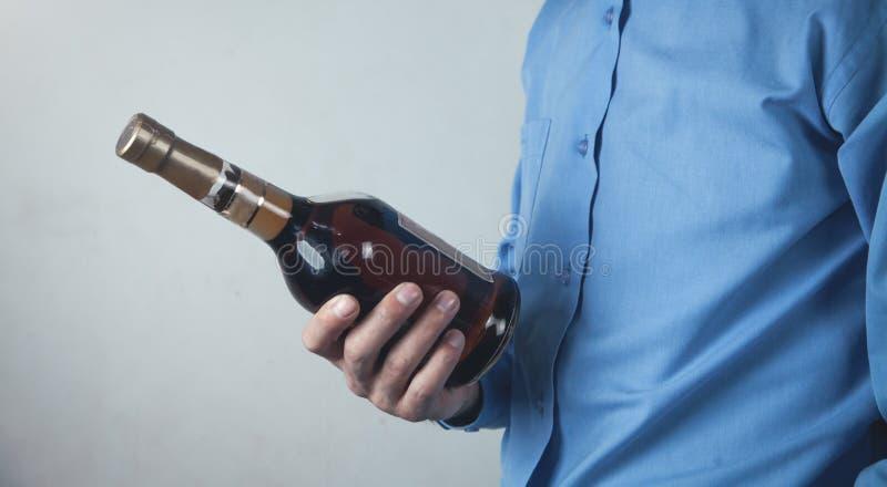 Un homme tient une bouteille de brandy photographie stock