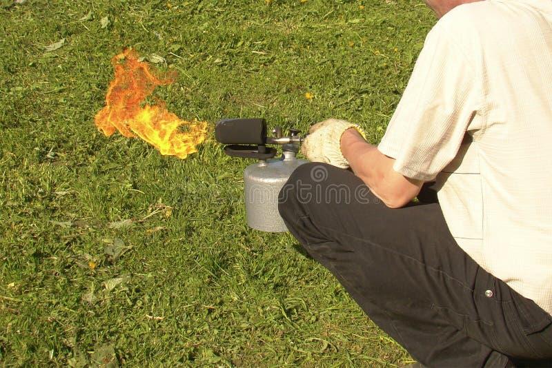 Un homme tient une lampe à souder brûlante dans des ses mains photo stock