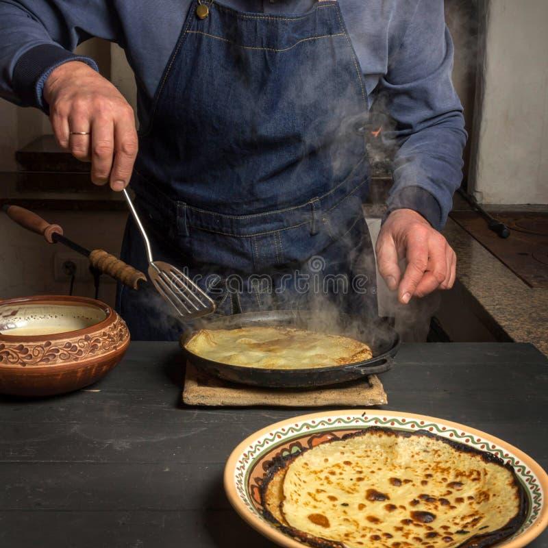 Un homme tourne une crêpe chaude sur une casserole avec une spatule photo libre de droits