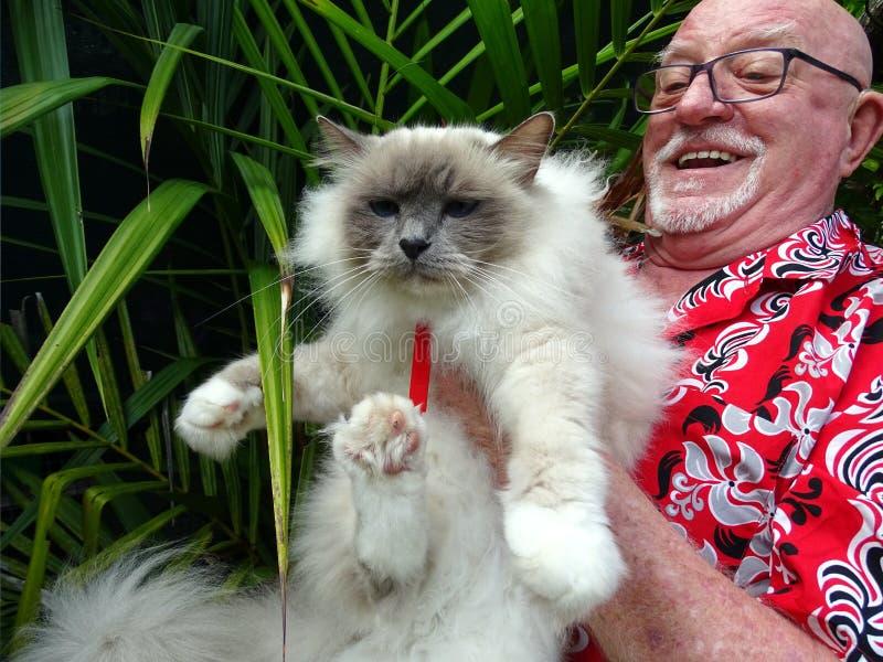 Un homme très heureux tenant son chat d'animal familier photos stock