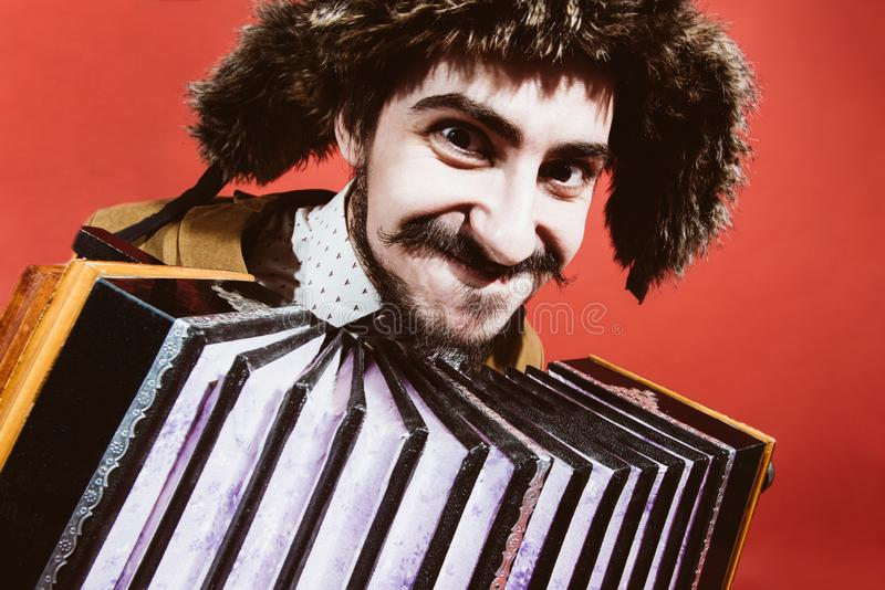 Un homme très positif avec un accordéon posant dans le studio photographie stock