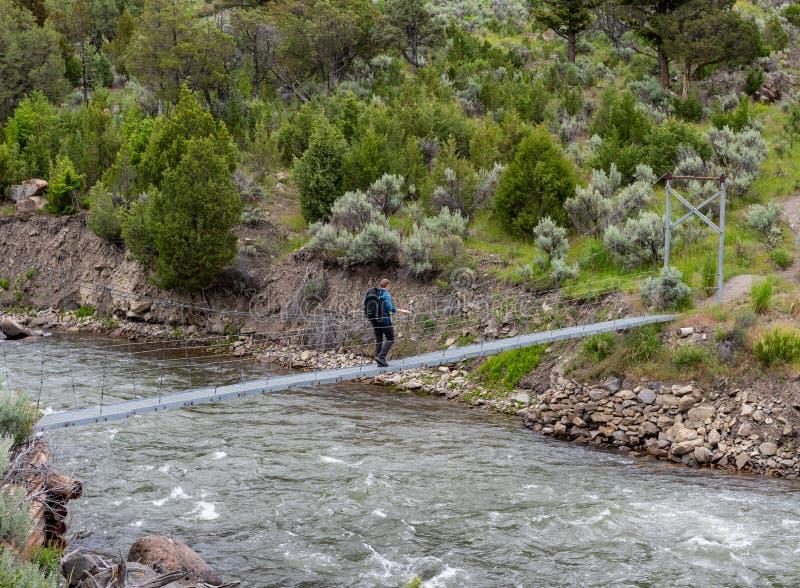Un Homme Traverse Le Pont Sur La Rivière Rushing images stock