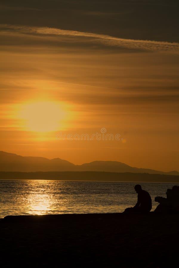 Un homme triste seul seul s'asseyant à la plage pendant le coucher du soleil Tiré au parc d'or de jardins à Seattle, Washington images stock