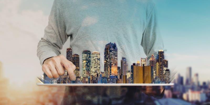 Un homme utilisant le comprimé numérique avec l'hologramme moderne de bâtiments Entreprise immobilière et investissement, technol image libre de droits