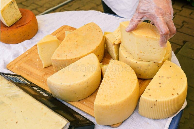 Un homme vend le fromage sur le marché de ville Différentes sortes de mensonge de fromage sur un conseil en bois Fromage coupé en image stock
