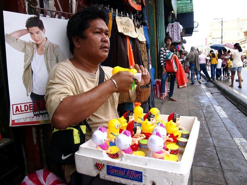 Un homme vend le genre différent de jouets à un trottoir photographie stock