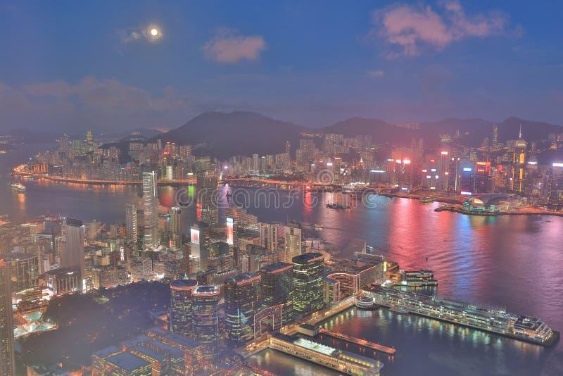un horizonte de Hong Kong en la noche con la luna fotos de archivo